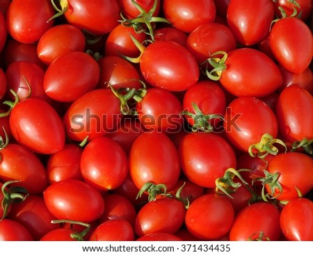 Bright red cherry tomatoes are being sold at a farmer market