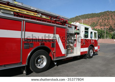 Bright red fire engine used to respond to emergency in mountain town. - stock photo