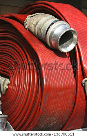 Bright red fire hose rolled up on a fire truck - stock photo