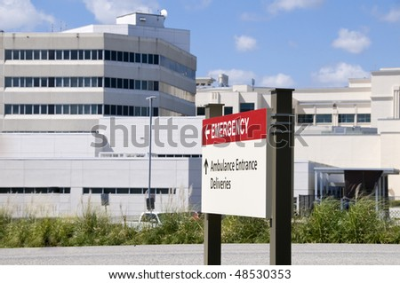 Bright red hospital Emergency entrance sign in front of a hospital building - stock photo