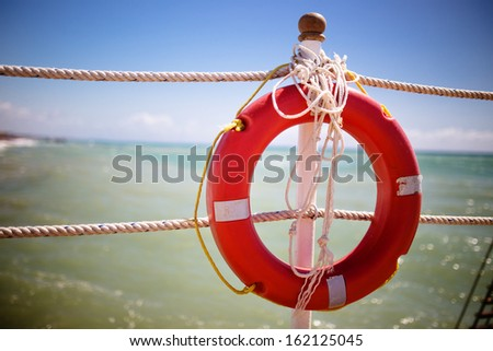 Bright red lifebuoy on the pier - stock photo