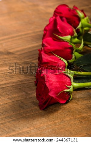 Bright red roses in a row on a wooden table - stock photo