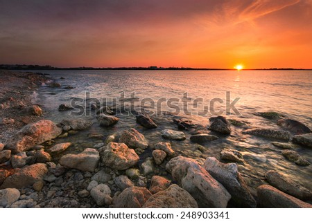 Bright red sunset sky over the Black Sea on the coast of the Crimean peninsula among marine stones - stock photo