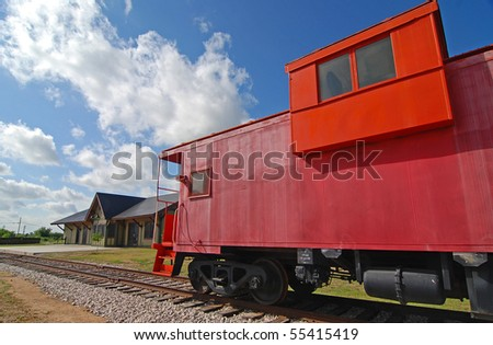 Bright red vintage caboose parked on railroad tracks near yellow railway depot.