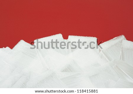 Bright red wall painted in white with paint roller. Brush strokes texture.