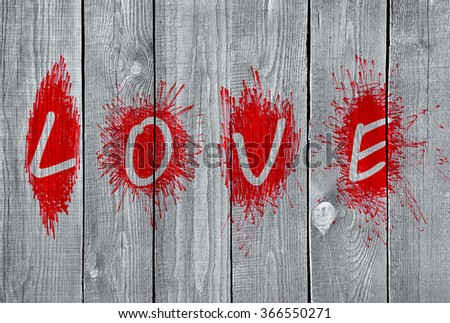 "Bright red word ""Love"" on a grey wooden wall  - stock photo"