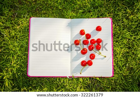 Bright ripe cherry on a background of pure Notepad - stock photo