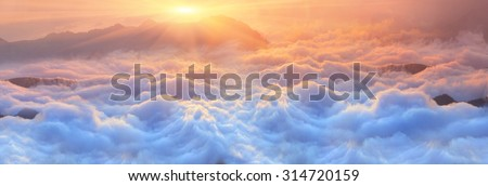 Bright saturated colors dawn above the sea of fog over the tops of the Carpathian is fabulously beautiful panoramic view, illuminated by the golden rays of the rising sun early in the morning - stock photo