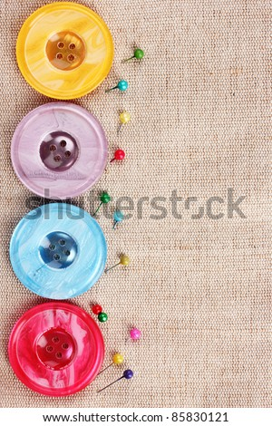 Bright sewing buttons on gray fabric - stock photo