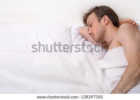 Bright shoot of upset man lies in the bed - stock photo