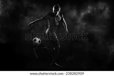 bright soccer playerl on the black background - stock photo