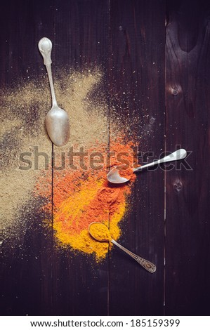 Bright spices and spilled curry powder, allspice, paprika and spoons fell on the wooden board