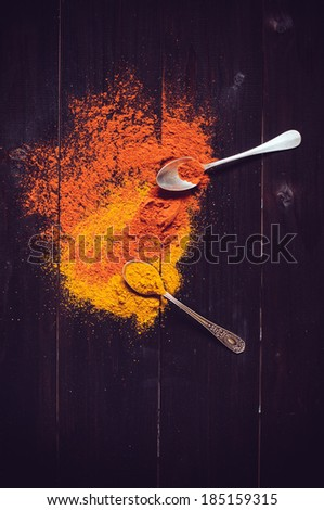 Bright spices and spilled curry powder, paprika and spoon fell on the wooden board - stock photo