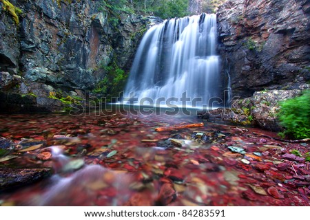 Bright stones shine through clear waters of Rockwell Falls in Glacier National Park - stock photo