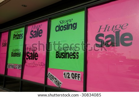 Bright store closing signs in a suburban shopping center. - stock photo