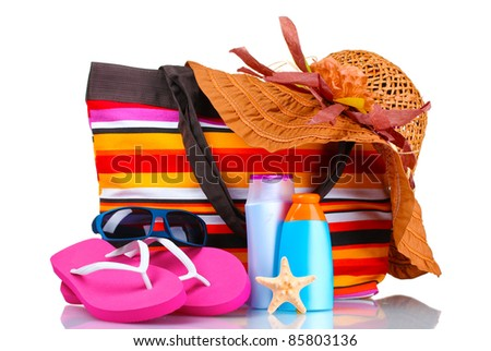 bright striped beach bag and beach items isolated on white