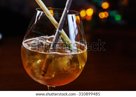 Bright strong alcoholic cocktail with a creative decoration of chocolate sticks and ice cubes on a table in a restaurant with backgrounds of colored disco lights soft focus and beautiful bokeh.