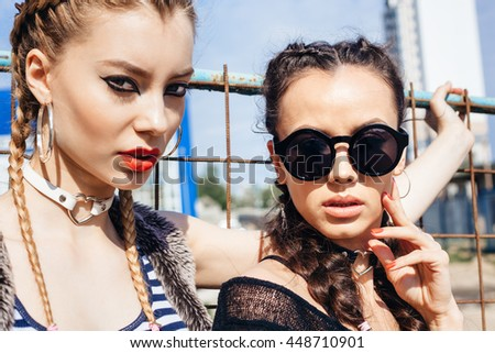 Bright stylish lifestyle outdoor portrait of two pretty best friends girls looking at camera