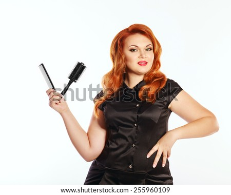 Bright stylish red-haired woman in professional attire. Barber, hair stylist Holding a comb - stock photo