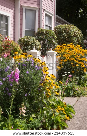 Bright summer flowers almost hide an old fashioned gate to a pink Victorian home. - stock photo