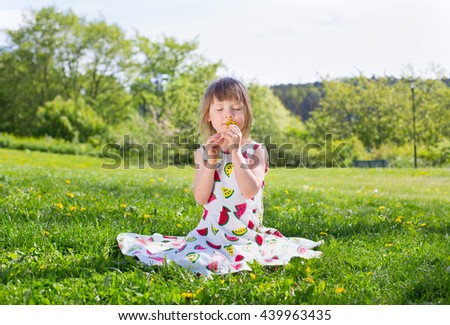 bright summer portrait of small adorable blond girl sitting on green lawn in multicolored drew with yellow dandelion - stock photo