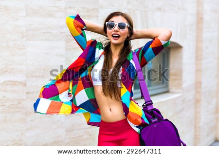 Bright summer trendy portrait of young fit girl walking on the street, wearing vivid shirt crop top and leg gins holding big sportive bag, long hairs and make up, smiling, screaming, joy. - stock photo