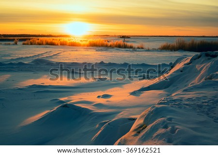 Bright sun at sunset in winter with large snow drifts. - stock photo