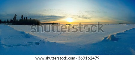Bright sun at sunset in winter with the road and the footprints in the snow. - stock photo