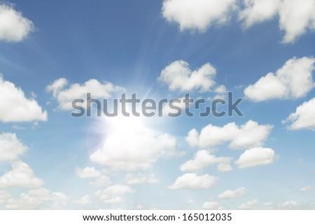 Bright sun in fluffy clouds sky - stock photo
