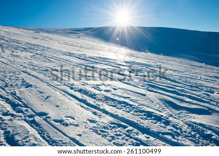 Bright sun in winter mountains covered with snow. - stock photo