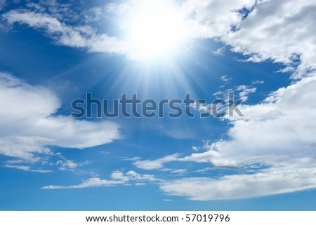 Bright sun shines through clouds in the blue sky