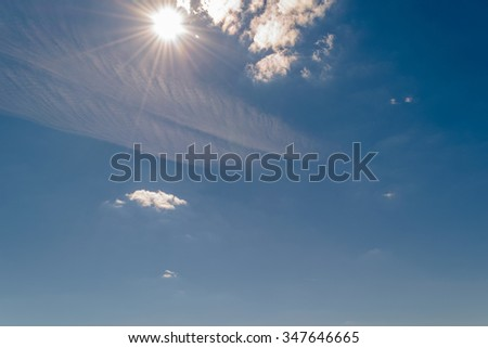 Bright sun shining in the sky with clouds on summer day - stock photo