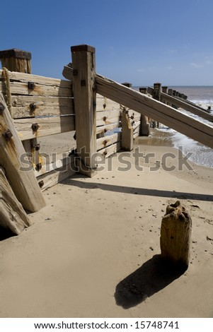 Bright sunny beach scene with decaying wooden revetments on the East Riding coastline at Spurn Point