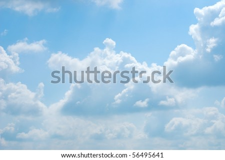 Bright sunny clouds against midday blue sky - stock photo
