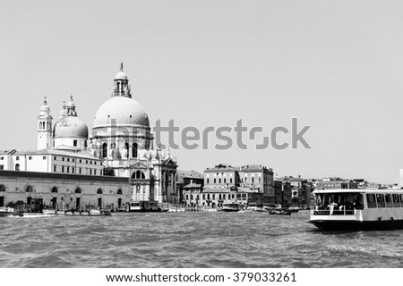 Bright sunny panorama view of The Grand Canal with gondola and Santa Maria della Salute church, Venice, Italy. Monochrome beautiful background of the venetian canal. Black and white photo. - stock photo
