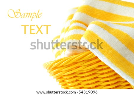 Bright sunny wicker basket filled with fresh clean towels.  Close-up on white background with copy space. - stock photo