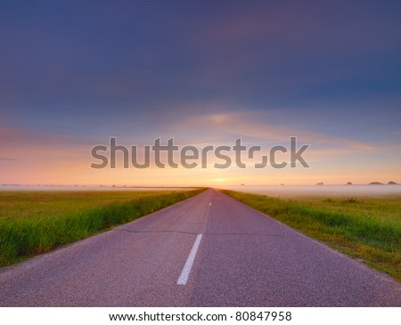 Bright sunrise over countryside empty road - stock photo