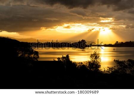 Bright sunset beams and dramatic sky, Lake Rotorua - New Zealand - stock photo