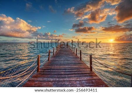 Bright sunset over sea pier - stock photo