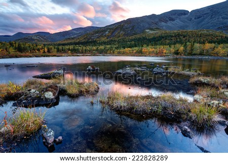 Bright sunset scene with sky reflected in Polygonal freshwater lake surrounded by autumn taiga forest in Hibiny mountains above the Arctic Circle - stock photo