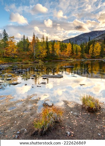 Bright sunset sky reflected in Polygonal freshwater lake surrounded by colorful taiga forest in Hibiny mountains above the Arctic Circle - stock photo