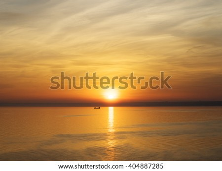 Bright sunset. Tranquil Sea. Fishing boat in the rays of the setting sun - stock photo