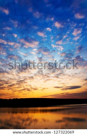 bright sunset with clouds above the lake - stock photo