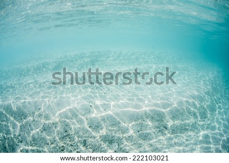 Bright sunshine ripples across white sand in the tropical Pacific Ocean. Coral colonies cannot grow on sand substrates because they are in continual motion. - stock photo