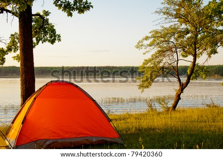 Bright tent by the picturesque lake around sunset - stock photo