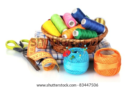 bright threads in basket, scissors and measuring tape isolated on white