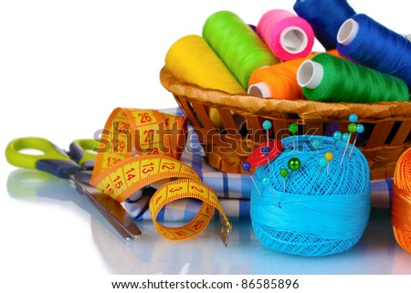 bright threads in basket, scissors and measuring tape isolated on white - stock photo