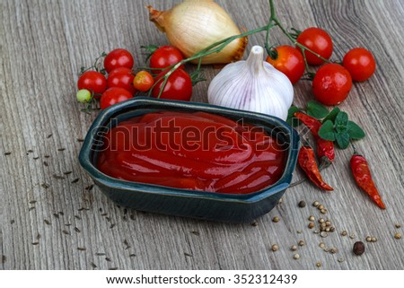 Bright Tomato ketchup with herbs and spices on the wood background - stock photo