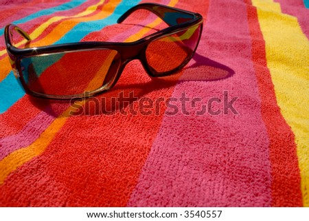 bright towel and sunglases - stock photo