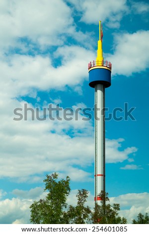 bright tower against the blue sky with white clouds - stock photo